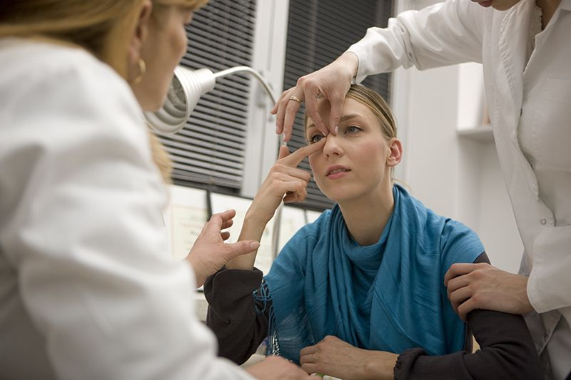 Woman having her nose examined by doctors