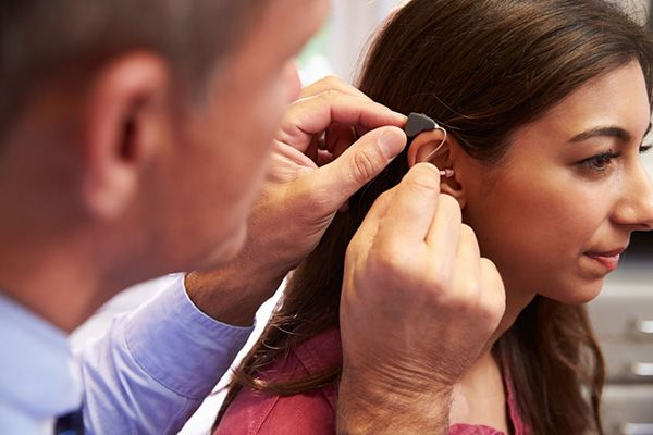 Audiologist fitting patient with hearing aid
