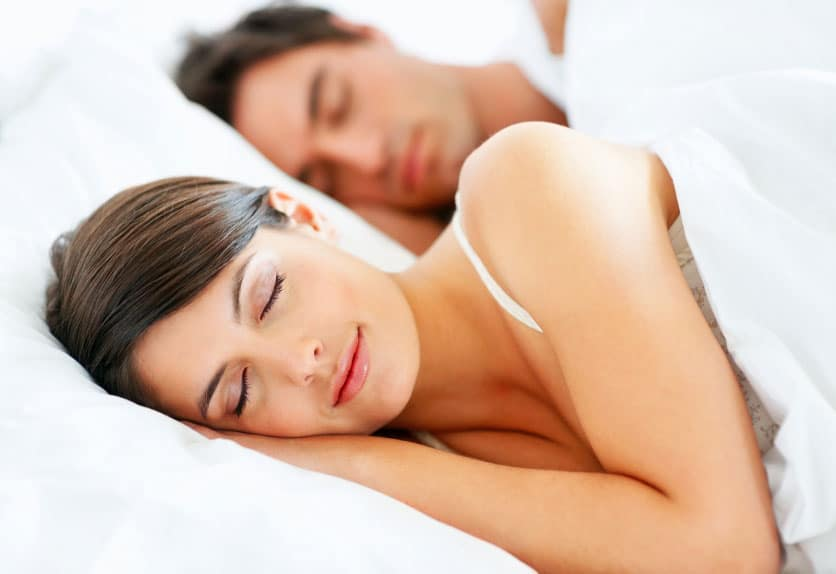 Woman and man sleeping on white sheets