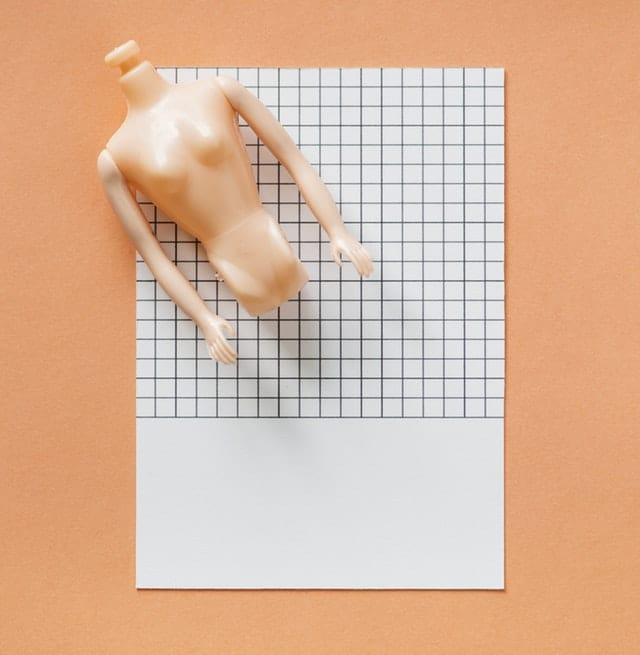 A doll torso on top of graph paper