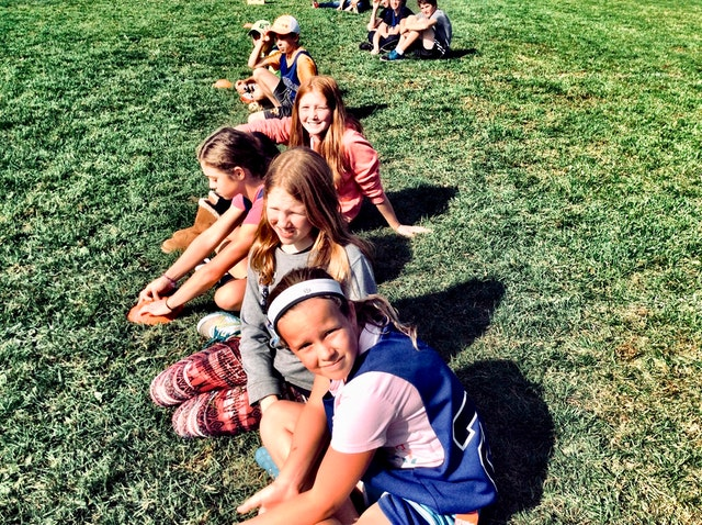 kids sitting on the grass at summer camp