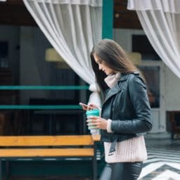 woman walking in public looking at cell phone