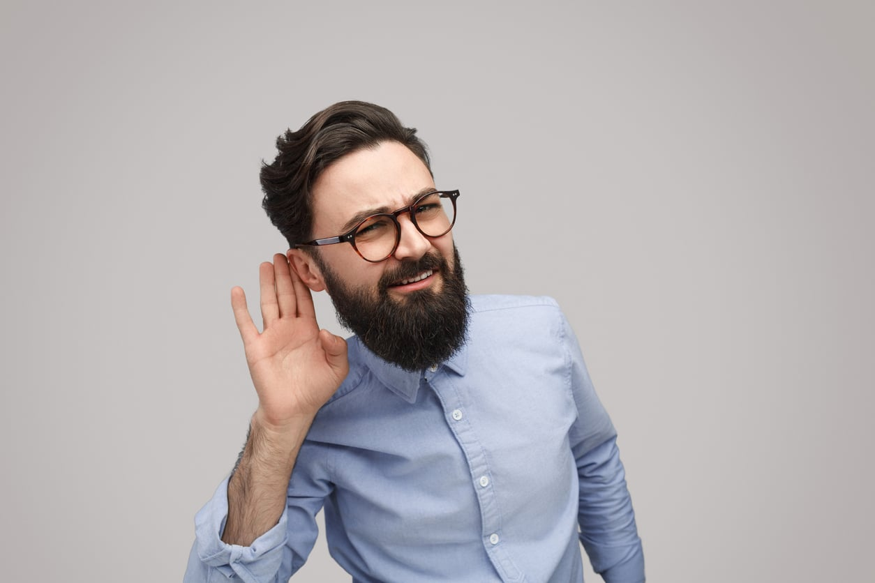 man putting hand up to ear in a listening fashion