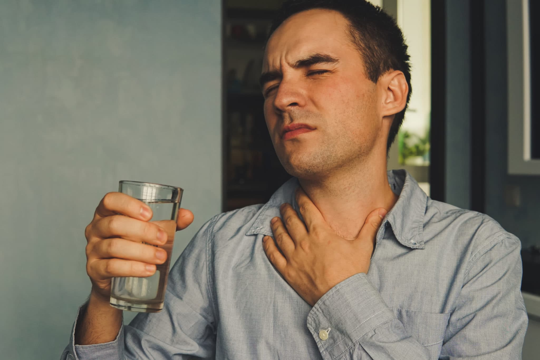 A parched throat and a glass of water in hand. Handsome guy in casual clothes is holding a glass of water and touching his throat while sitting on couch at home.