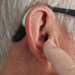 Older man touching his hearing aid while it's in his ear