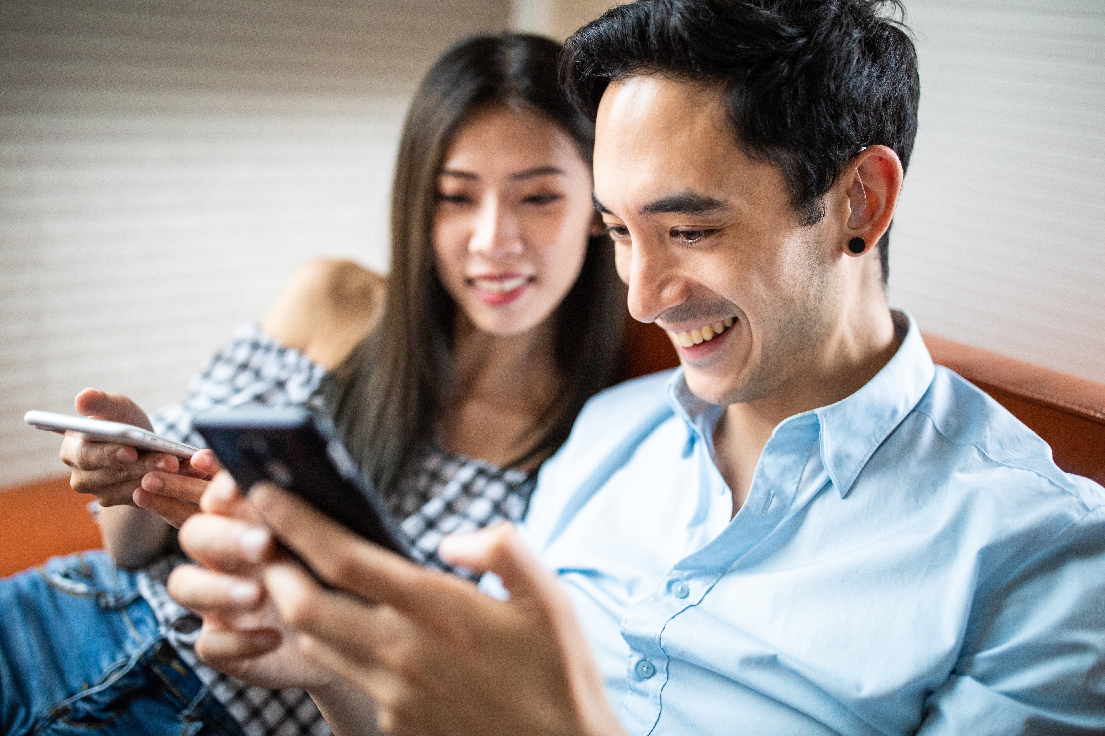 Couple relaxing together, man wearing hearing aids
