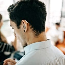 Younger man wearing a hearing aid while using a smartphone.